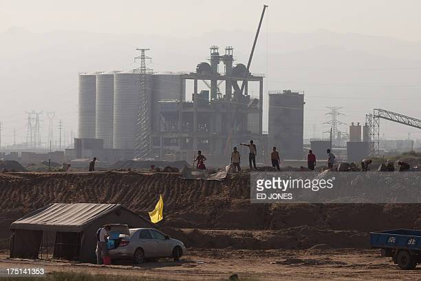 Photo taken on August 19, 2012 shows workers before a refinery near a 'toxic lake' near the inner Mongolian city of Baotou. On the edge of the...