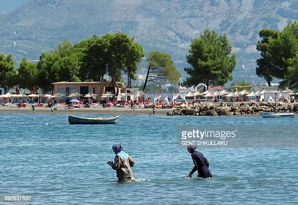 A photo taken on August 19 2016 shows two covered women wearing hijabs swimming in the sea at Shengjin beach near the city of Lezhe The ban on the...