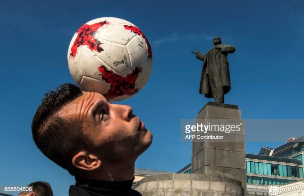 A photo taken on August 19 2017 shows a performer playing with a football in downtown Yekaterinburg Yekaterinburg and its arena will host several...