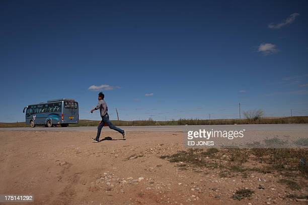 Photo taken on August 20, 2012 shows a man running from a bus at a roadside near a state-owned rare earth mine north of the inner Mongolian city of...