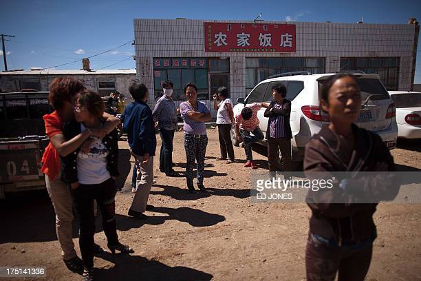 Photo taken on August 20, 2012 shows people standing next to a roadside restaurant near a state-owned rare earth mine north of the inner Mongolian...