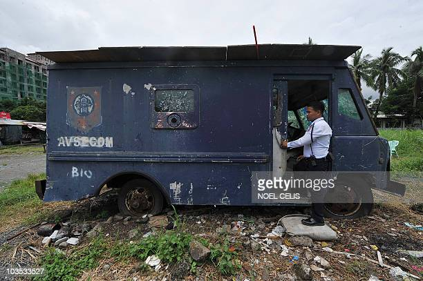 A photo taken on August 21 shows a security guard standing next to an Aviation Security Command van allegedly used to carry the body of late senator...