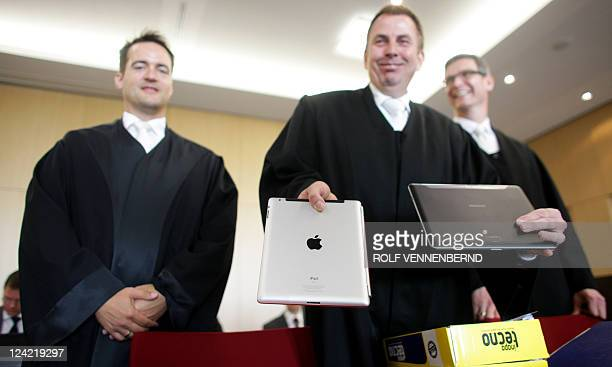 A photo taken on August 25 2011 shows Samsung's lawyers Eike Schaper Thomas Musmann and Henrik Timmann showing a Apple iPad computer tablet and a...