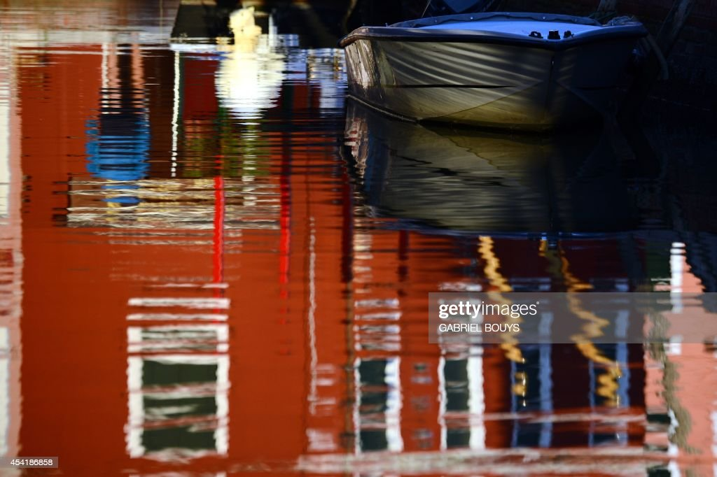 A photo taken on August 25, 2014 shows colored houses, reflecting on water in Burano, an island in the Venetian lagoon. Burano is known for its small, brightly painted houses. The colors of the houses follow a specific system originating from the golden age of its development. People wishing to paint a house must send a request to the government, which will respond by giving certain colors permitted for that lot.