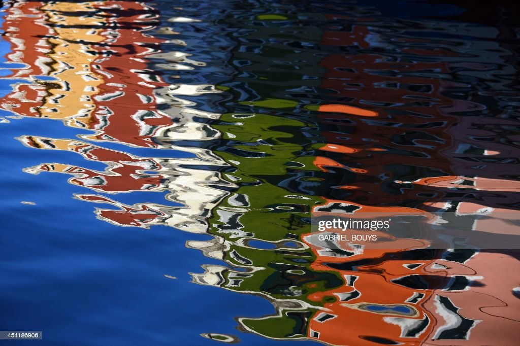 A photo taken on August 25, 2014 shows colored housesreflecting on water in Burano, an island in the Venetian lagoon. Burano is known for its small, brightly painted houses. The colors of the houses follow a specific system originating from the golden age of its development. People wishing to paint a house must send a request to the government, which will respond by giving certain colors permitted for that lot.