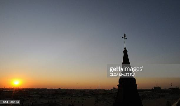 A photo taken on August 6 2014 shows a roof climber at the top of a spire in the center of the Russian city of Saint Petersburg The city has long...