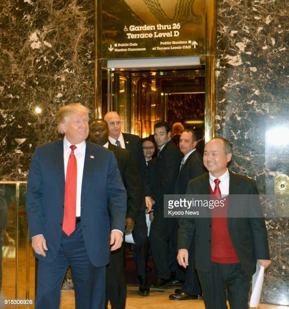 Photo taken on Dec 6 2016 shows US Presidentelect Donald Trump walking with Softbank Group Corp CEO Masayoshi Son at Trump Tower in New York ==Kyodo