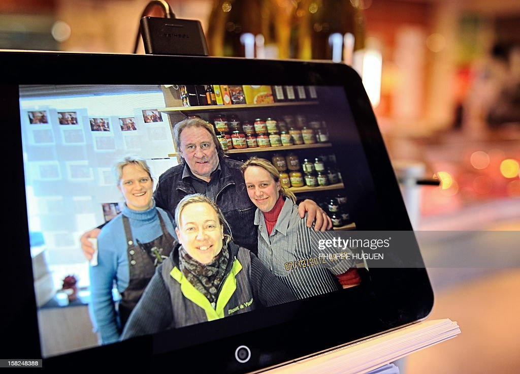 A photo taken on December 12, 2012 in the Belgian village of Estaimpuis shows a photo on a tablet featuring French actor Gerard Depardieu (C) posing on December 7 with the local butcher and her emp...