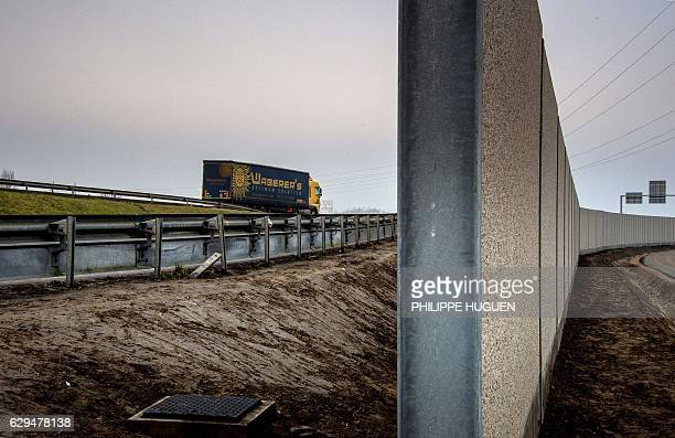 TOPSHOT A photo taken on December 13 2016 in Calais shows a fourmetrehigh wall running along a kilometrelong stretch of the main road leading to...