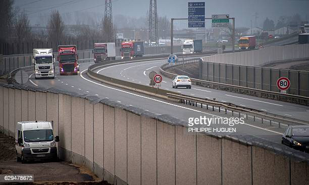 A photo taken on December 13 2016 shows a fourmetrehigh wall running along a kilometrelong stretch of the main road leading to Calais port aimed at...