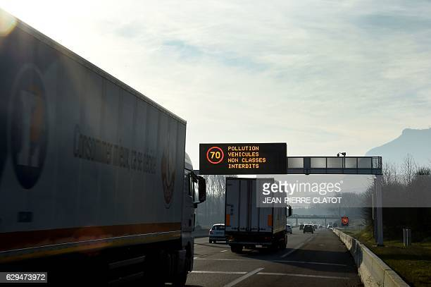 A photo taken on December 13 2016 shows vehicles on a highway while a board displays traffic reduction measures near the city of Grenoble eastern...