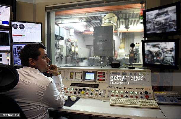 A photo taken on December 18 2014 in ViryChatillon south of Paris shows an engineer working on a test bench a Renault Sport F1 engine The general...