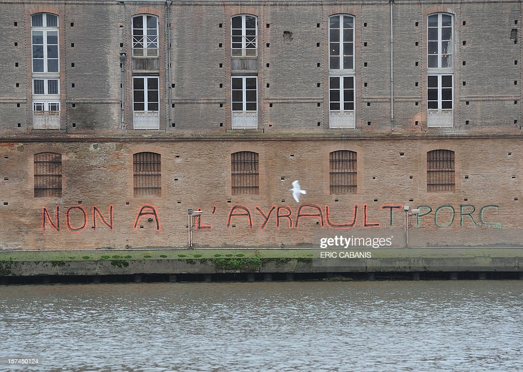 A photo taken on December 3, 2012 shows an inscription on a wall of the Hotel-Dieu, on the banks of the river Garonne in Toulouse, southern France, denouncing French Prime Minister and former Mayor of Nantes Jean-Marc Ayrault plans to build a new airport in the French western city of Notre-Dame-des-Landes. The 580-million-euro ($747-million) project was approved in 2008, with construction expected to start in 2014.