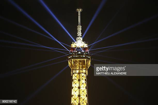 TOPSHOT A photo taken on December 6 2015 in Paris shows the Eiffel Tower illuminated by French artist Yann Toma and architects from Artel The...