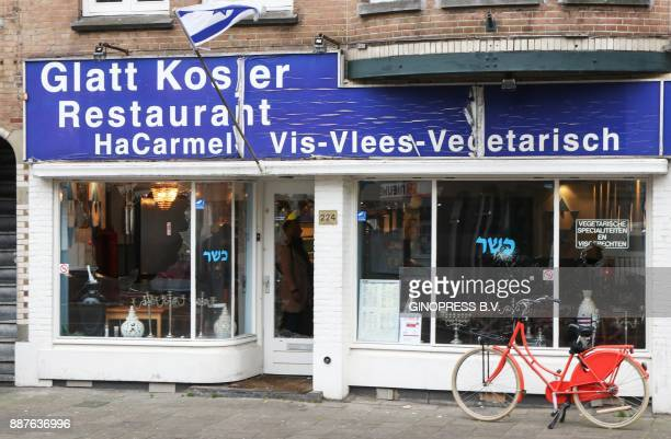 A photo taken on December 7 2017 shows the damaged storefront of kosher Jewish restaurant HaCarmel in Amsterdam A man shown holding a Palestinian...