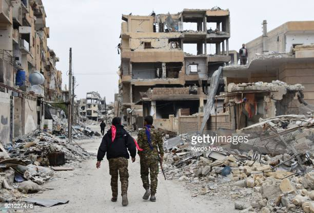 Photo taken on Feb 16 shows Kurdish fighters walking in Raqqa northern Syria following the recapture of the selfproclaimed capital of the Islamic...