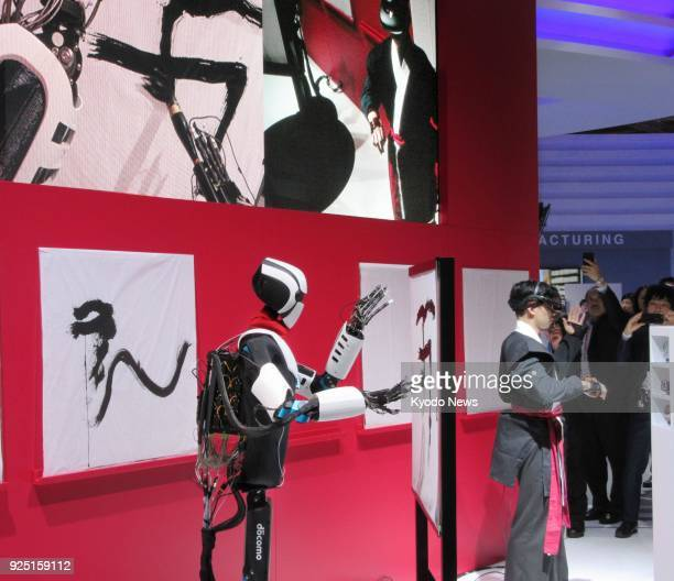 Photo taken on Feb 26 2018 at Mobile World Congress in Barcelona shows a calligraphy demonstration using an NTT Docomo humanoid robot that employs 5G...