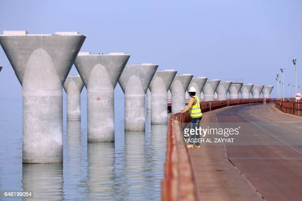 A photo taken on February 11 2017 in Kuwait City shows a labourer standing at a construction site of the Sheikh Jaber AlAhmad AlSabah causeway one of...