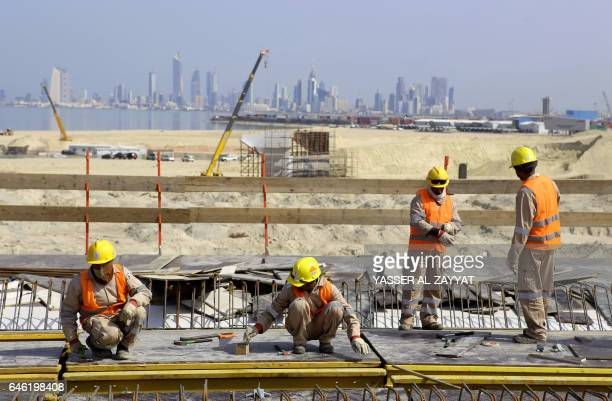 A photo taken on February 11 2017 in Kuwait City shows labourers working at a construction site of the Sheikh Jaber AlAhmad AlSabah causeway one of...