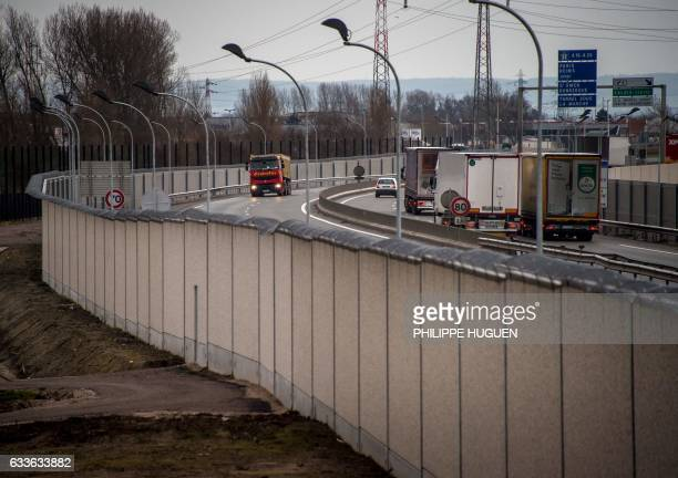 A photo taken on February 2 2017 in Calais shows trucks on a road next to a fourmetrehigh wall running along a kilometrelong stretch of the main road...