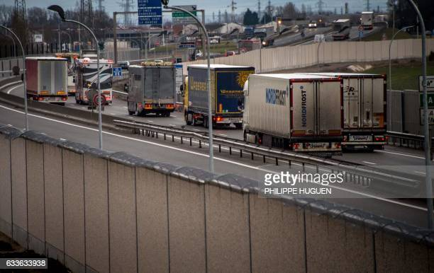 Photo taken on February 2, 2017 in Calais, shows trucks on a road next to a four-metre-high wall, running along a kilometre-long stretch of the main...