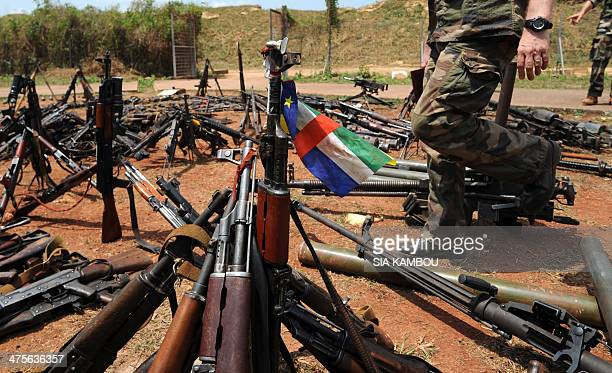 Photo taken on February 28 2014 shows a Central African flag placed on a gun among other arms confiscated from exSeleka rebels and Antibalaka militia...