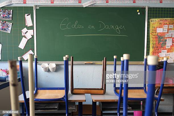 A photo taken on February 8 2016 shows the words 'School in danger' written on the blackboard of a classroom at 'Jean Perrin' elementary school in...