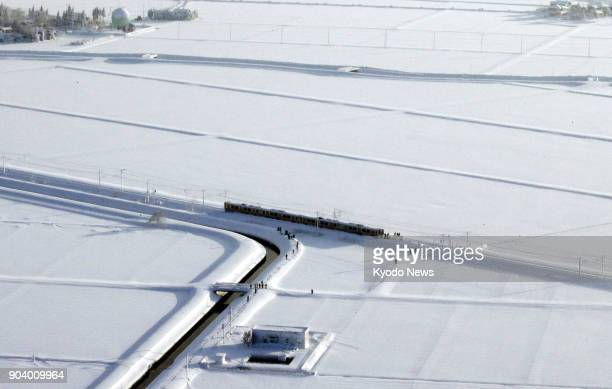 Photo taken on Jan 12 from a Kyodo News plane shows a fourcar train on East Japan Railway Co's Shinetsu Line that was stranded between stations in...