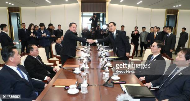 Photo taken on Jan 9 in Panmunjeom shows Cho Myoung Gyon South Korea's minister of unification shaking hands with Ri Son Gwon chairman of North...