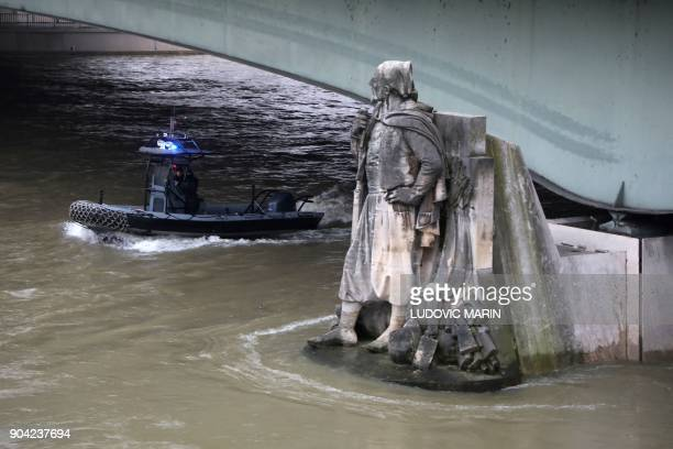 A photo taken on January 12 2018 shows waters of the river Seine whose level has risen near the statue of the Zouave at the Alma bridge in Paris...