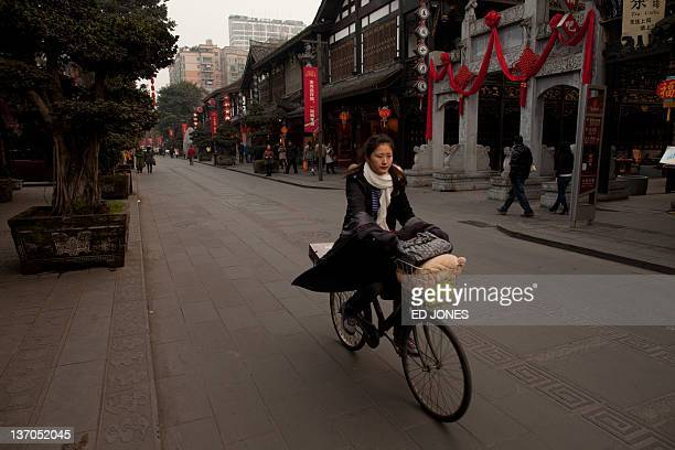A photo taken on January 14 2011 shows a woman riding a bicycle on a street in Chengdu Sichuan province The capital of Sichuan Chengdu and its...