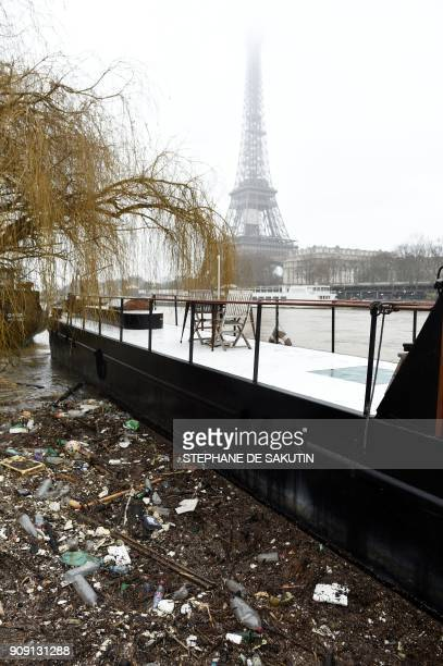 A photo taken on January 23 2018 shows detritus gathered next to a houseboat docked on a flooded bank as the river Seine level has risen in front of...