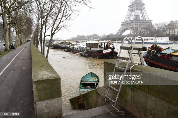 A photo taken on January 23 2018 shows flooded banks and houseboats docked as the river Seine level has risen in front of the Eiffel tower in Paris /...