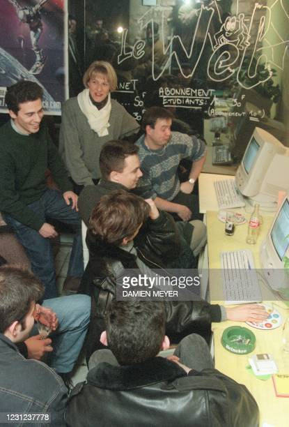 Photo taken on January 24, 1996 of a group of young people gathered in front of a computer in a cybercafé in the city of Besançon, while the book by...