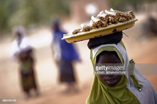 A photo taken on January 24 2014 shows a peanuts street seller in Leo Burkina Faso The French cosmetics company L'Occitane has been working with...