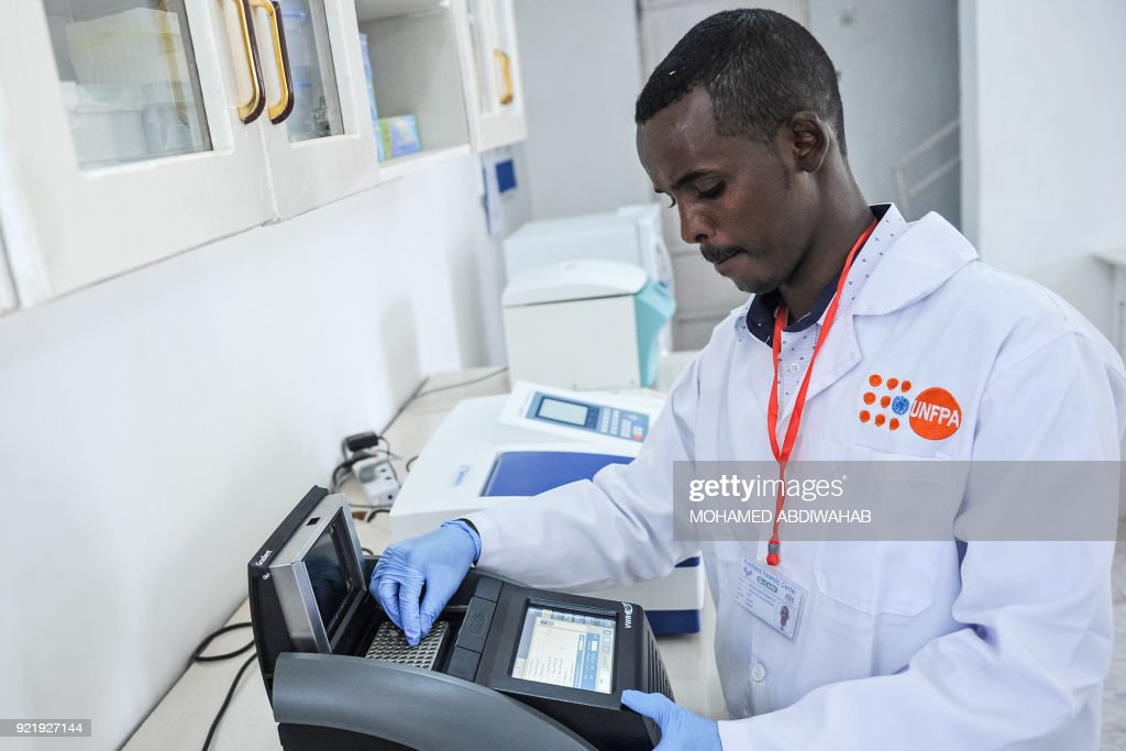 A photo taken on January 24, 2018 shows a laboratory technician Abdulkadir Abdullahi Mohamed demonstrating DNA testing at the Puntland Forensic Center in Garowe, Puntland State, Somalia. The first Forensic Center in Somalia, partly funded by the Swedish government and supported by the United Nations Population Fund (UNFPA), brings advanced DNA testing capabilities to a country still lacking in paved roads and reliable electricity. The hope is that the DNA sample will help convict the woman's rapist, ushering in a new era of justice for the victims of Somalia's widespread sexual violence. / AFP PHOTO / Mohamed ABDIWAHAB