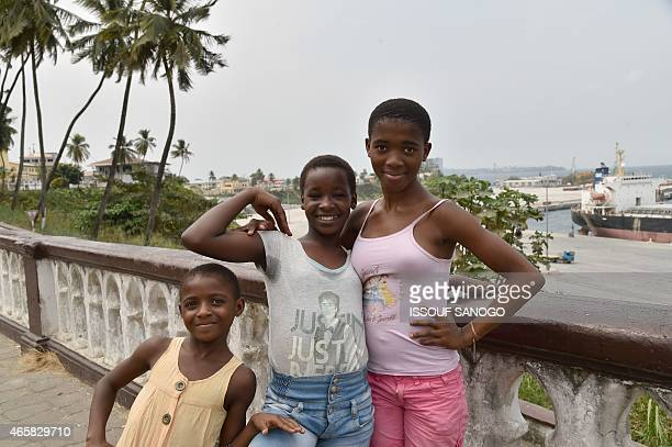 Photo taken on January 25 2015 show youngsters posing with a view of Malabo's Port in Equatorial Guinea in the background AFP PHOTO / ISSOUF SANOGO