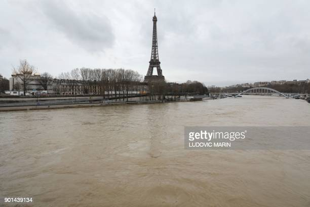 A photo taken on January 5 2018 shows waters of the river Seine which level has risen in front of the Eiffel tower in Paris following heavy rains...