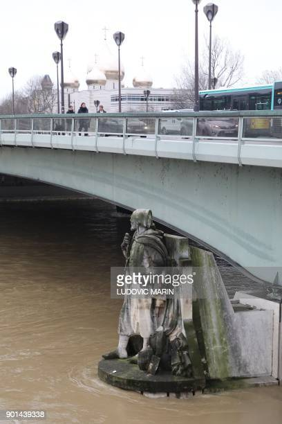 A photo taken on January 5 2018 shows waters of the river Seine which level has risen near the statue of the Zouave at the Alma bridge in Paris...