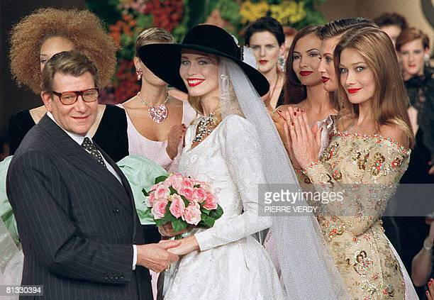 Photo taken on July 10 1996 shows French fashion designer Yves Saint Laurent posing with models Claudia Schiffer and Carla Bruni during the...