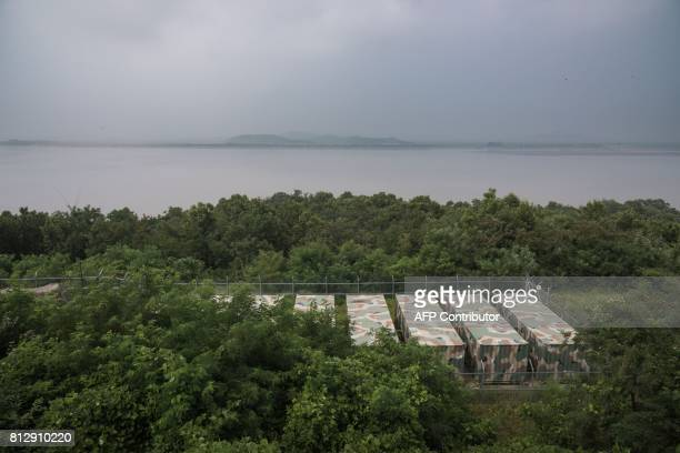 A photo taken on July 11 2017 shows South Korean military containers before the Demilitarized Zone and the shoreline of North Korea on the island of...
