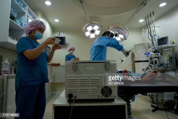 photo taken on July 12 2013 shows doctors performing a liposuction procedure at the JK Medical Group plastic surgery hospital in Seoul Skilled...