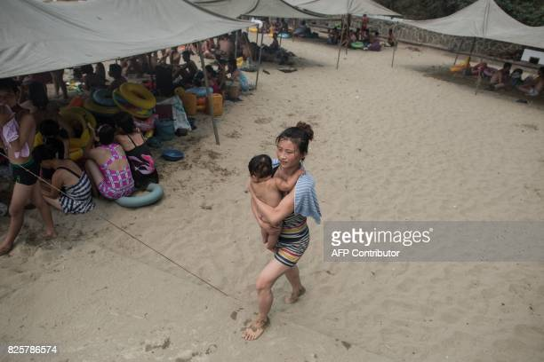 A photo taken on July 22 2017 shows a woman carrying a child at the West Sea Barrage beach outside the coastal city of Nampho southwest of Pyongyang...
