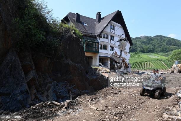 Photo taken on July 23, 2021 shows men driving on a destroyed road to Altena near the destroyed building of the country guest house 'Jaegerstuebchen'...