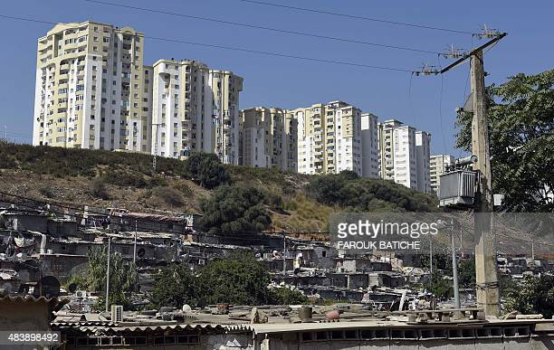 A photo taken on July 28 2015 shows a slum in front of buildings in the Ain ElMalha suburb of the Algerian capital Algiers Faced with a burst in...