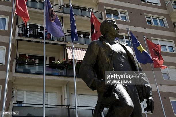 Photo taken on July 29 2014 shows Kosovo and Albanian flags flying behind a statue of a former Kosovo Liberation Army commander in Pristina Leaders...