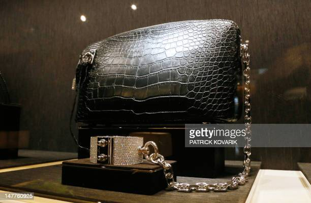 Photo taken on July 3, 2012 shows an alligator skin handbag with golden manacle with diamonds presented at the first Louis Vuitton jewellery store...