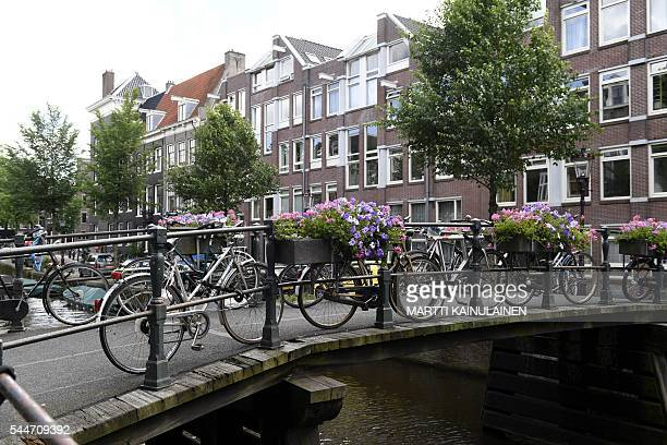 A photo taken on July 3 2016 shows bikes parked on the bridge crossing the canal in Amsterdam / AFP / Lehtikuva / Martti Kainulainen / Finland OUT
