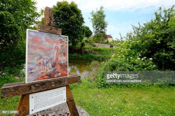 A photo taken on June 1 2017 shows a reproduction of the painting The WasherWomen displayed in a garden in Essoyes central eastern France where...