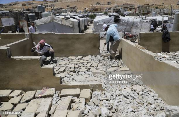 A photo taken on June 10 2019 shows workers demolishing a concrete shelter at a refugee camp in the northeastern Lebanese town of Arsal in the Bekaa...